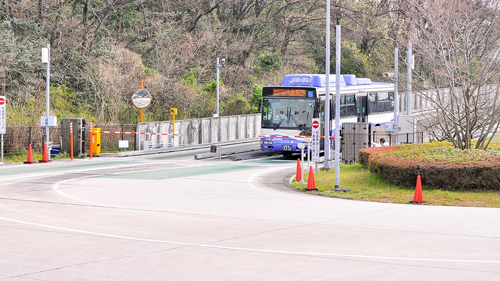 下りGB-2110形車輛が小幡緑地に設けられたモードインターチェンジのゲートでガイド輪を収納しているところ。データ通信により車輛番号、乗務員ID、ガイド輪の収納が確認されると手前のバーが上がり、路線バスとして走行を始める。