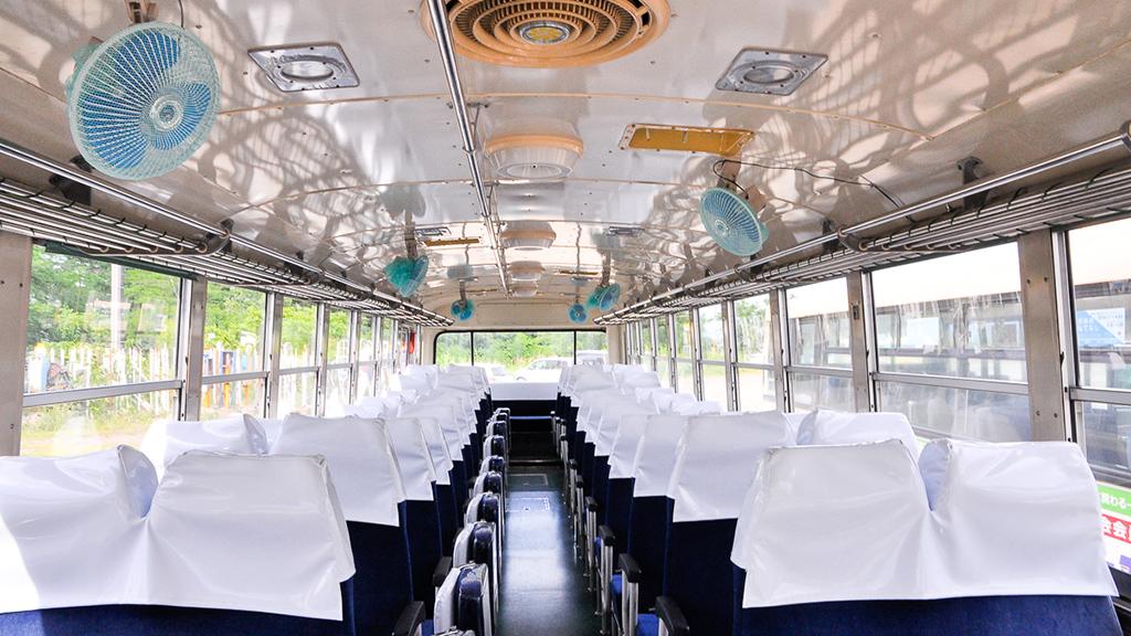 室内には2人掛けの前向きシートが左右にズラリと並んでいる。なお右側シート(画面では左側)は補助席付だ。訪ねたのが夏だったこともあり、後付けの扇風機が仮設されていた。