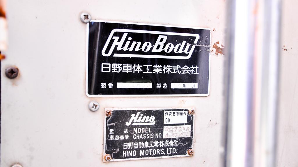 前の出入口左側面に貼られた銘板。シャーシが「日野自動車工業」で、ボディが「日野車体工業」製なのが解る。